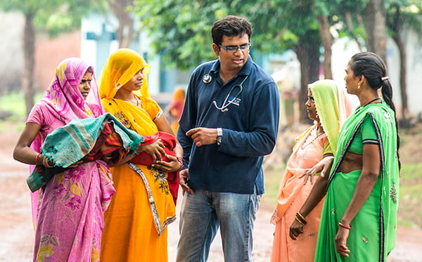 Dr. Sanket Patel talking to Indian women in colourful dresses