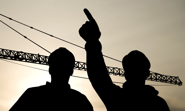Silhouettes of two men on worksite