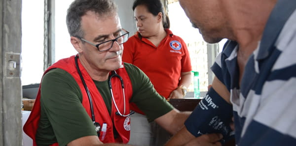 Red cross aid worker checking blood pressure